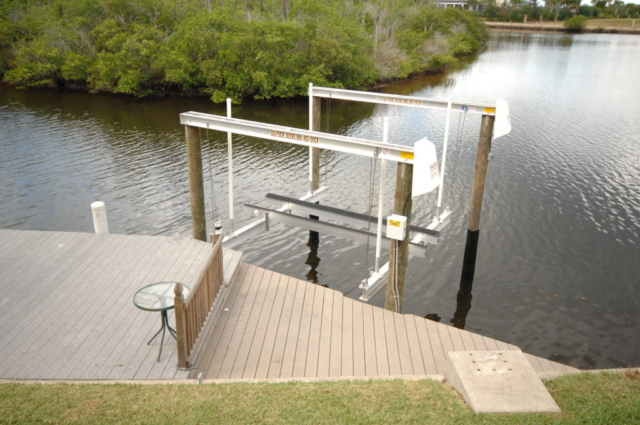 A Golden aluminum boat lift with a flat plate assembly attached to an angled stationary dock