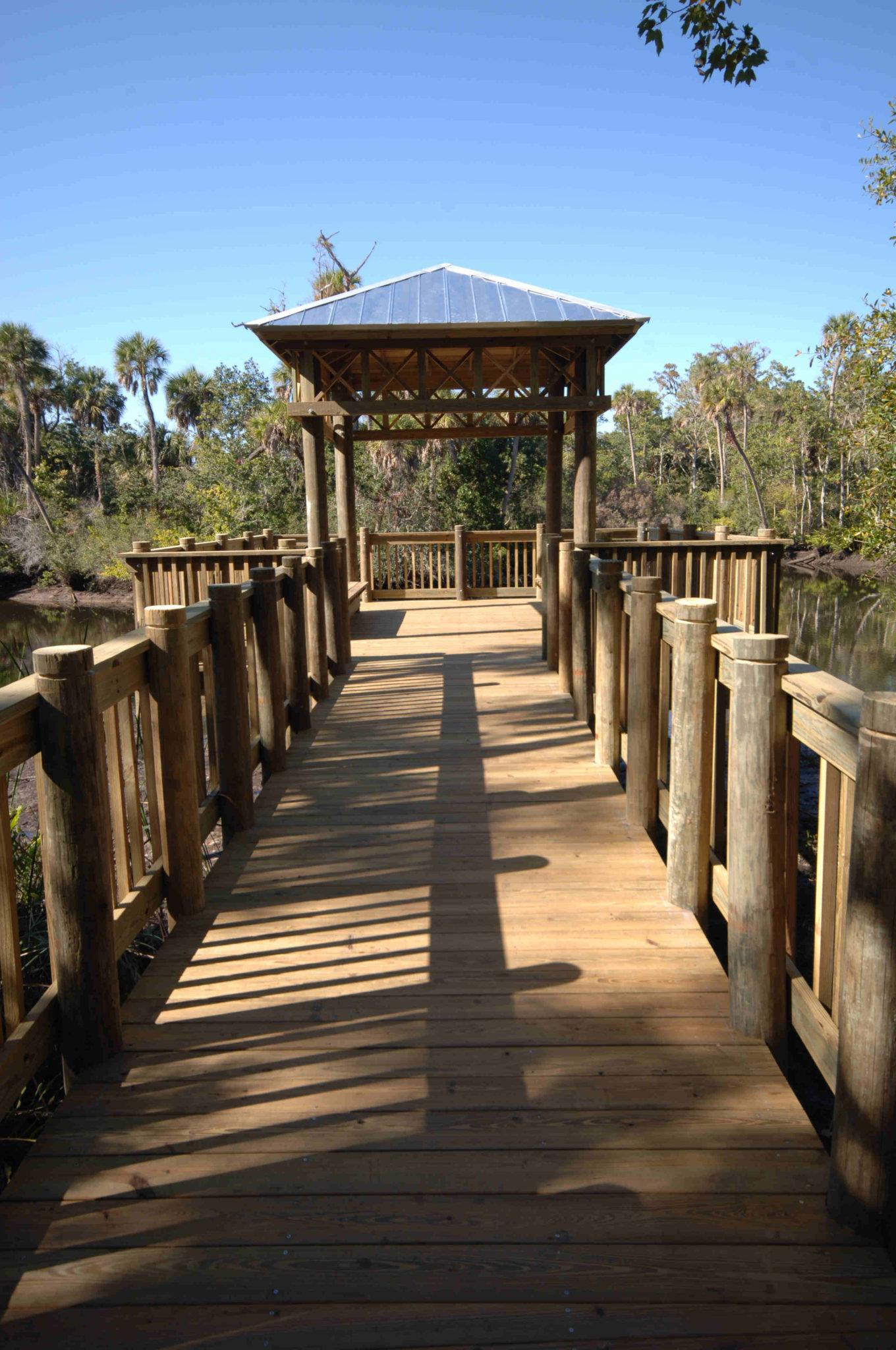 A timber boardwalk with gazebo roof at end of boardwalk in a park