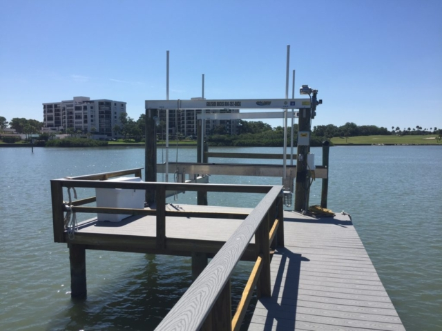 A Golden 4-post aluminum boat lift at end of composite stationary dock