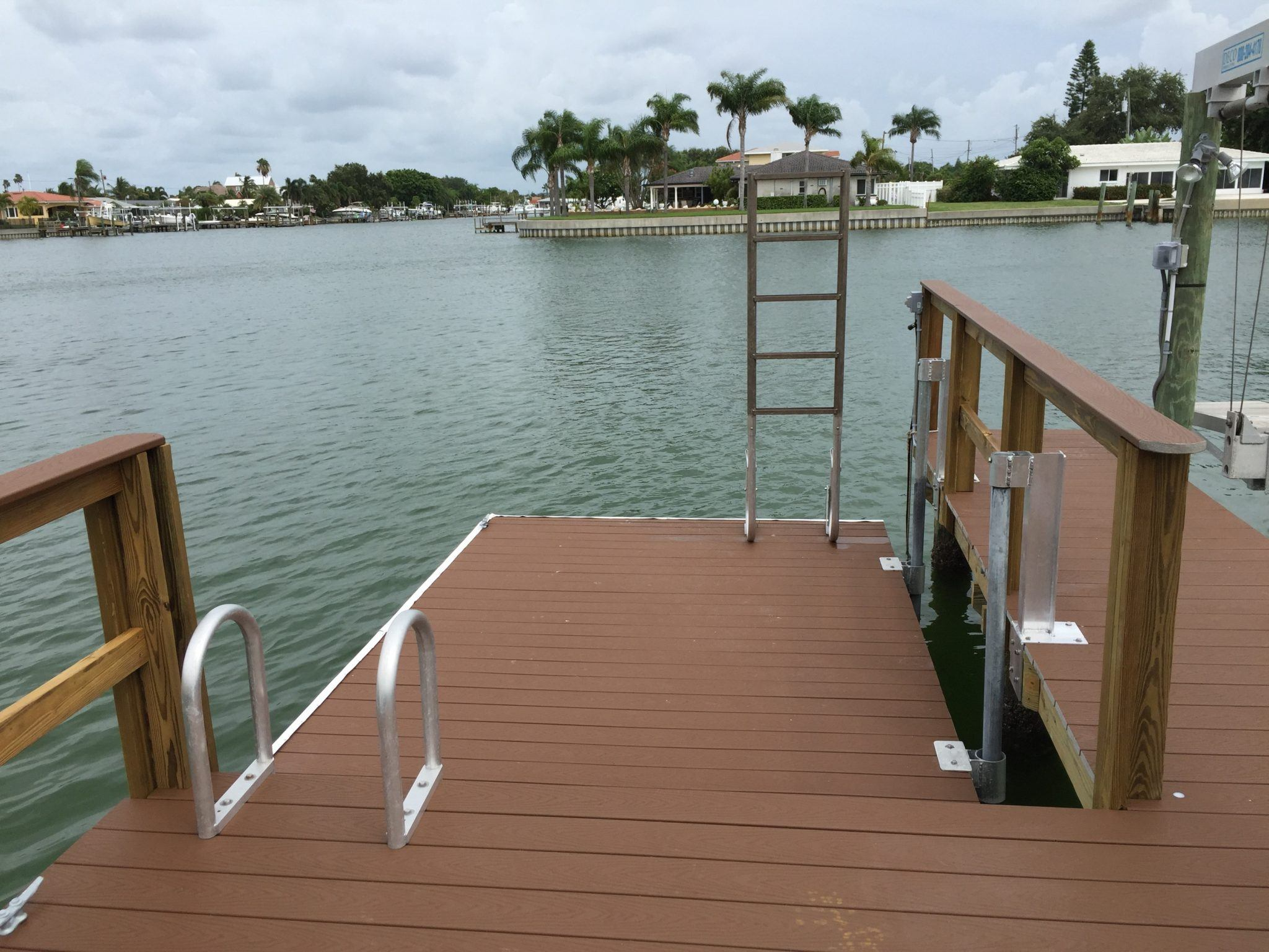 A new Trex floating dock attached to stationary dock with pipe slides and an aluminum ladder