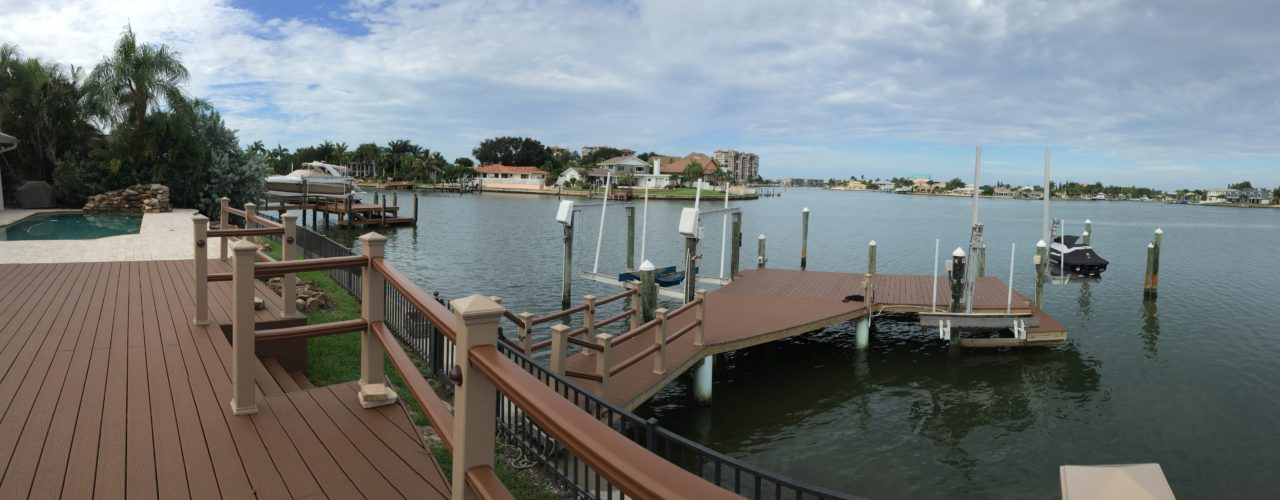 A Trex composite stationary dock and matching deck with Trex composite handrail on the water