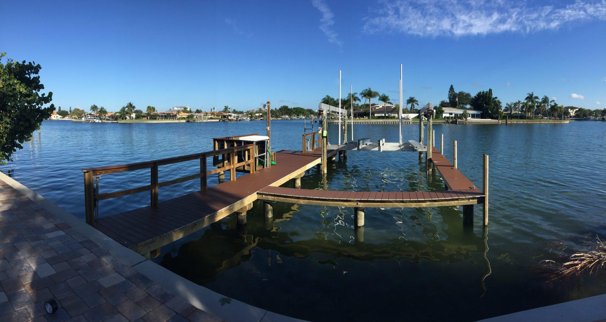 A Trex stationary dock with a catwalk around a aluminum boat lift on the water