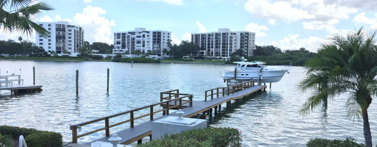 A long Trex stationary dock with an aluminum Golden boat lift on the water