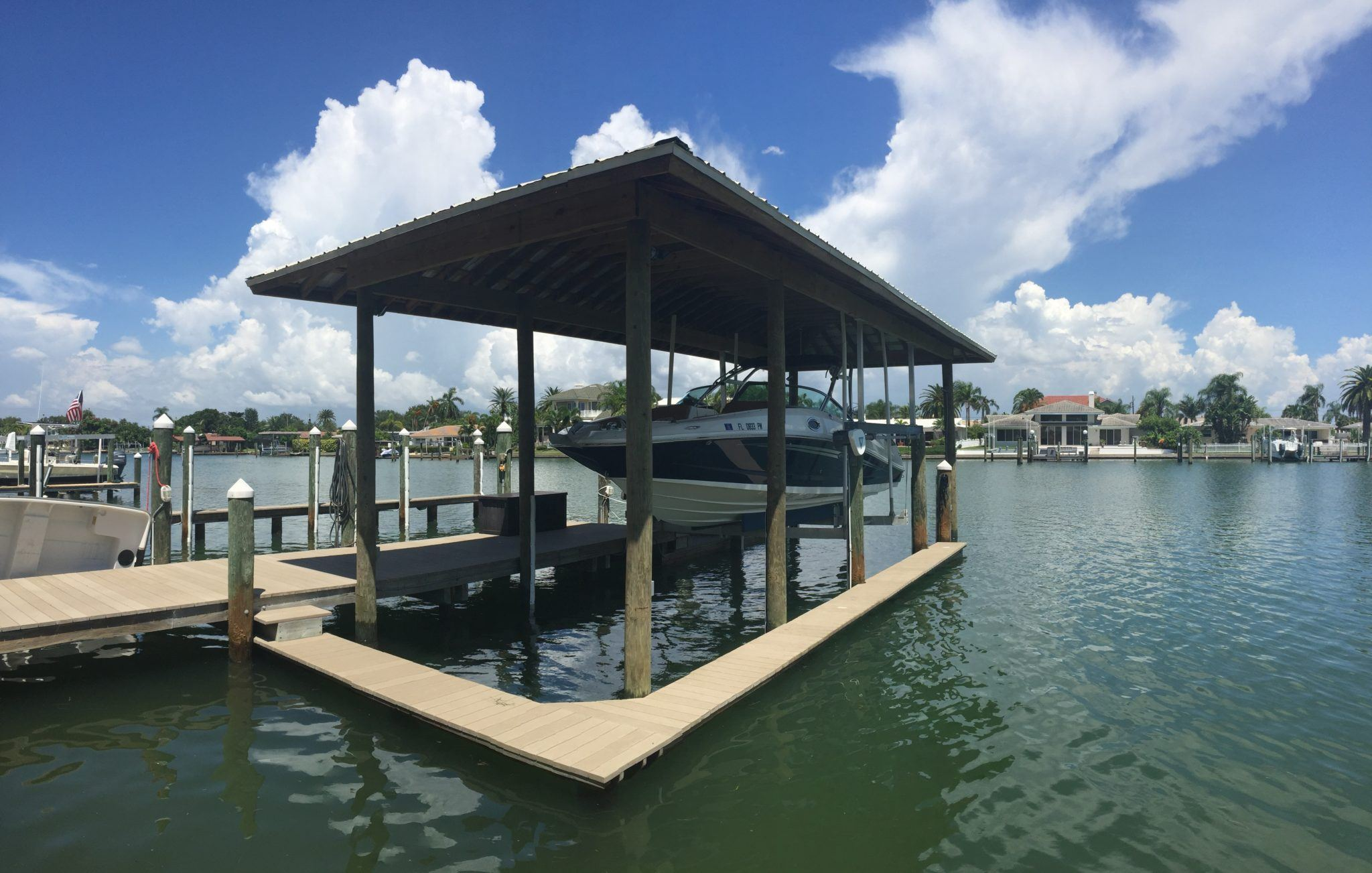 A hip style roof over an aluminum boat lift with a catwalk on the water