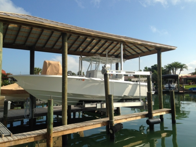 A Golden aluminum boat lift with a large hip style roof over it at a stationary dock