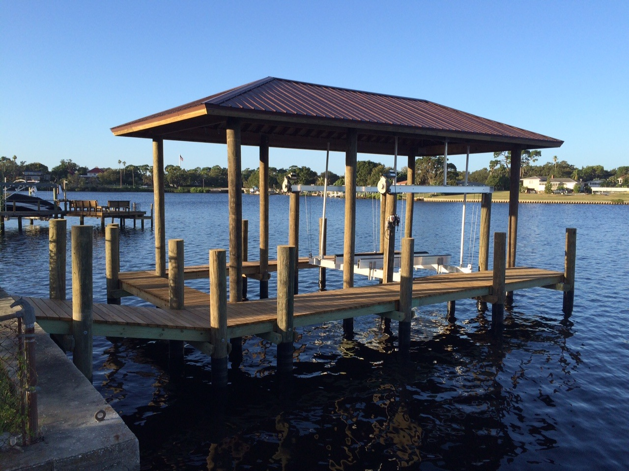 A Golden aluminum boat lift with a hip style roof over it with a stationary dock
