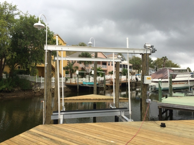 A aluminum boat lift with direct drive assembly with wharf lights attached
