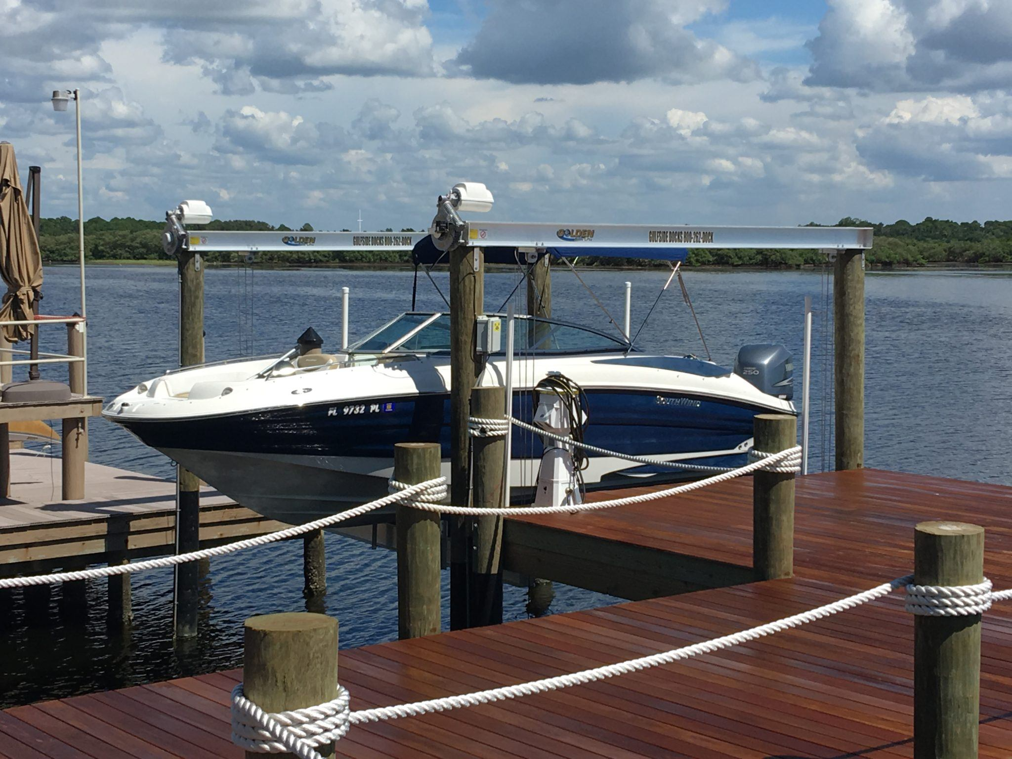 A Golden aluminum boat lift with Golden Sea-Drives attached to a stationary dock