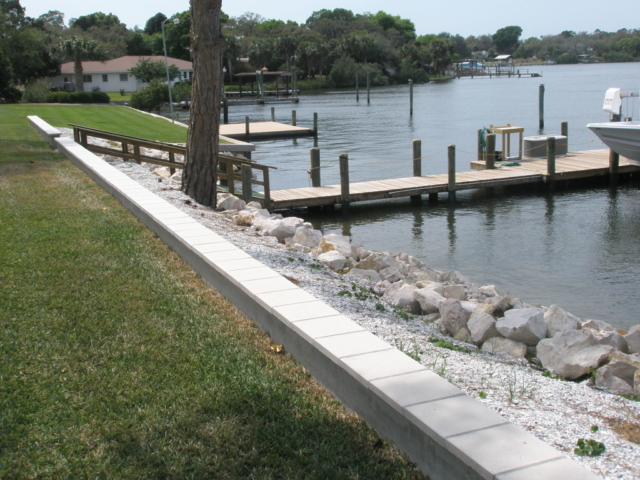 Residential limestone rip rap along shoreline with a stationary dock on the water