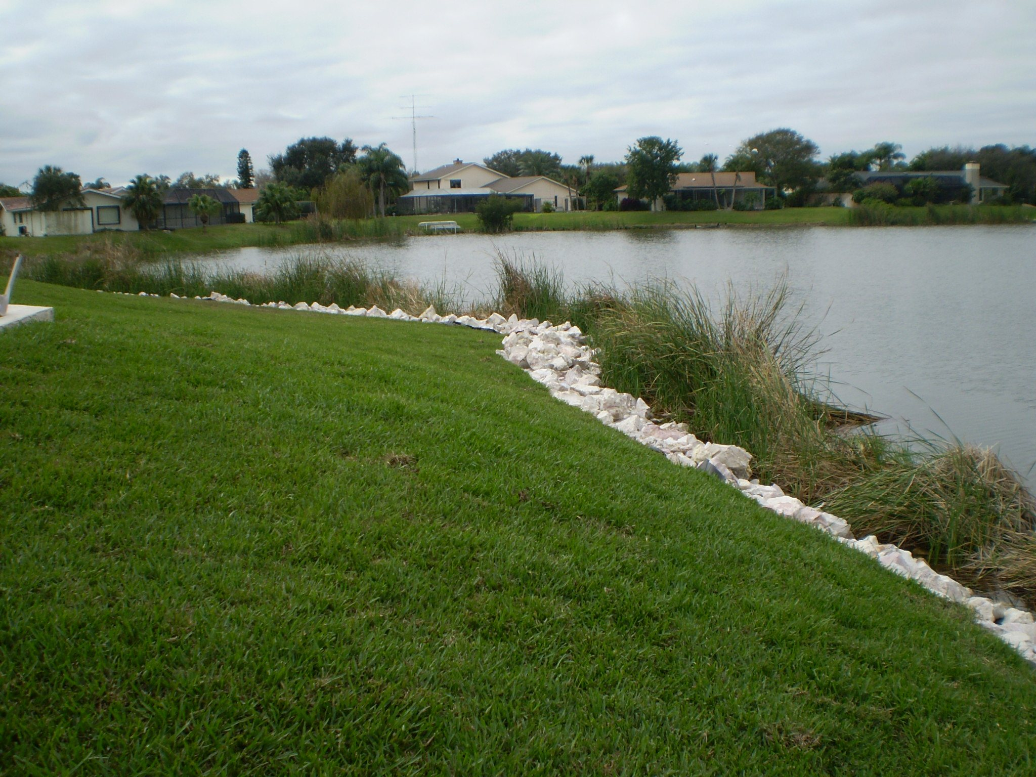 Limestone rip rap rock along shoreline of lake at a golf course