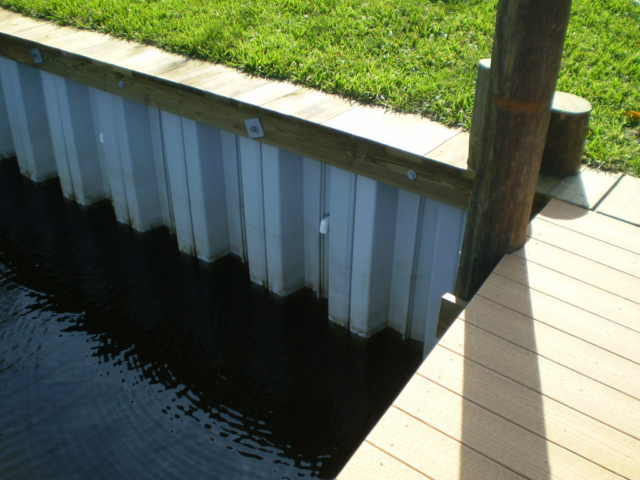 A vinyl seawall with a wooden cap on waterfront property