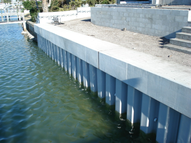 A vinyl seawall with a large concrete cap on the water