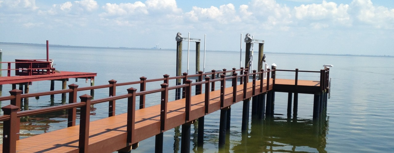 A Trex composite stationary dock with Trex composite handrail on the water