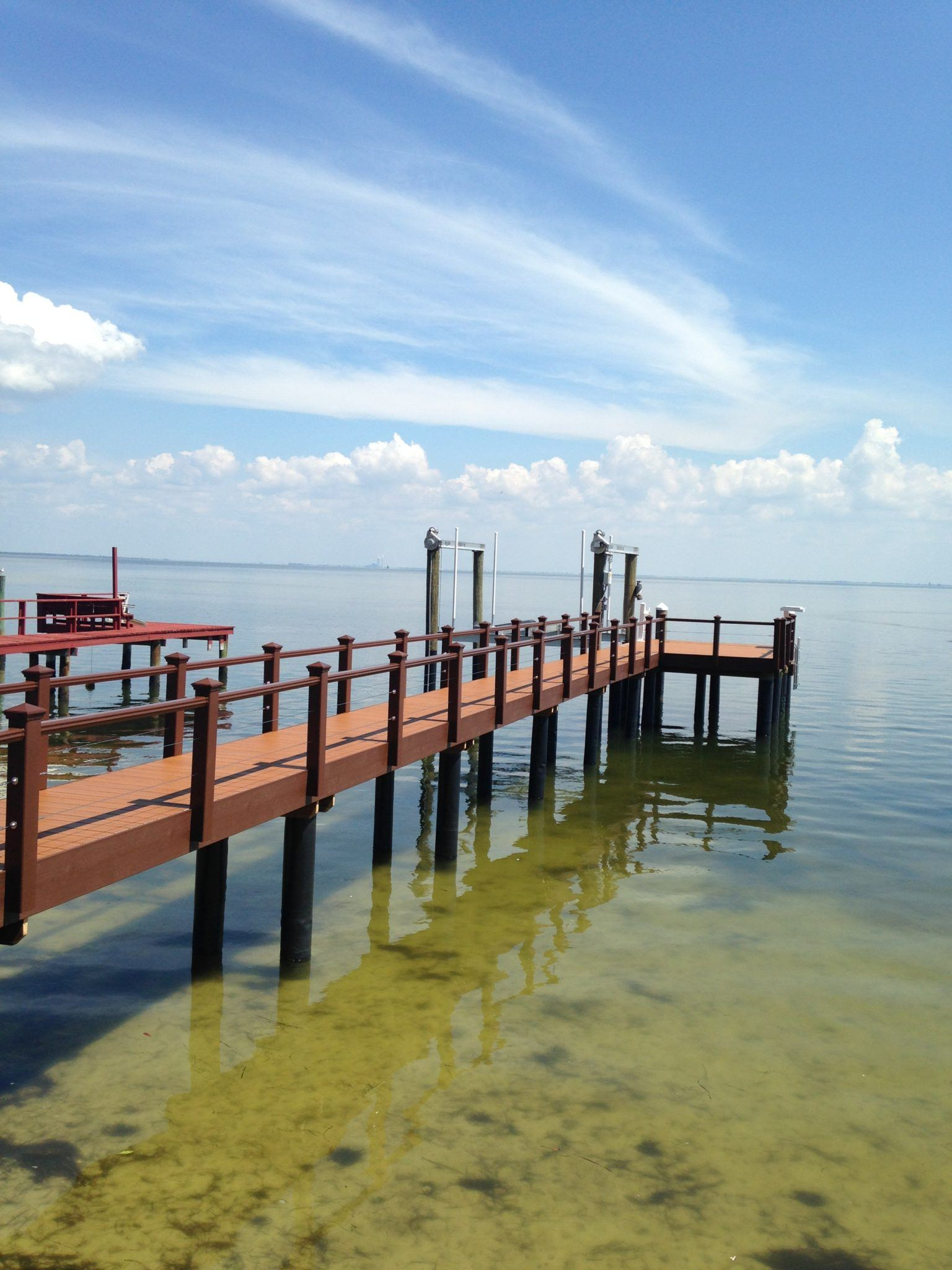 A new Trex dock with Trex composite handrail with cable railing and a boat lift on the water