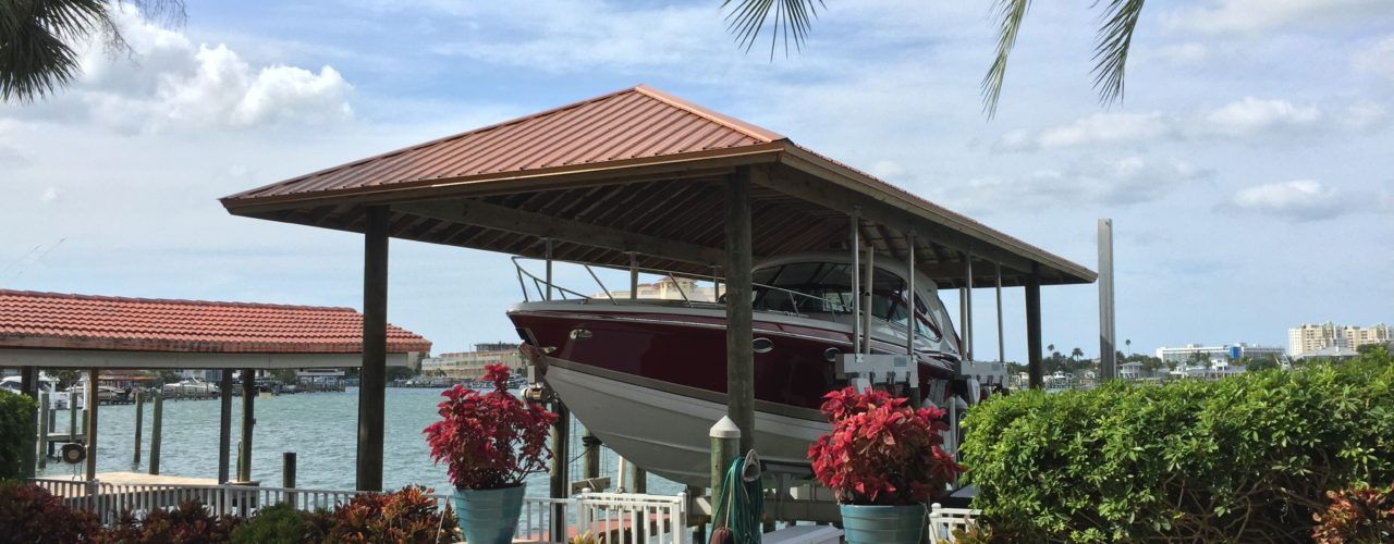 A hip style roof made out of metal over a boat lift on the water