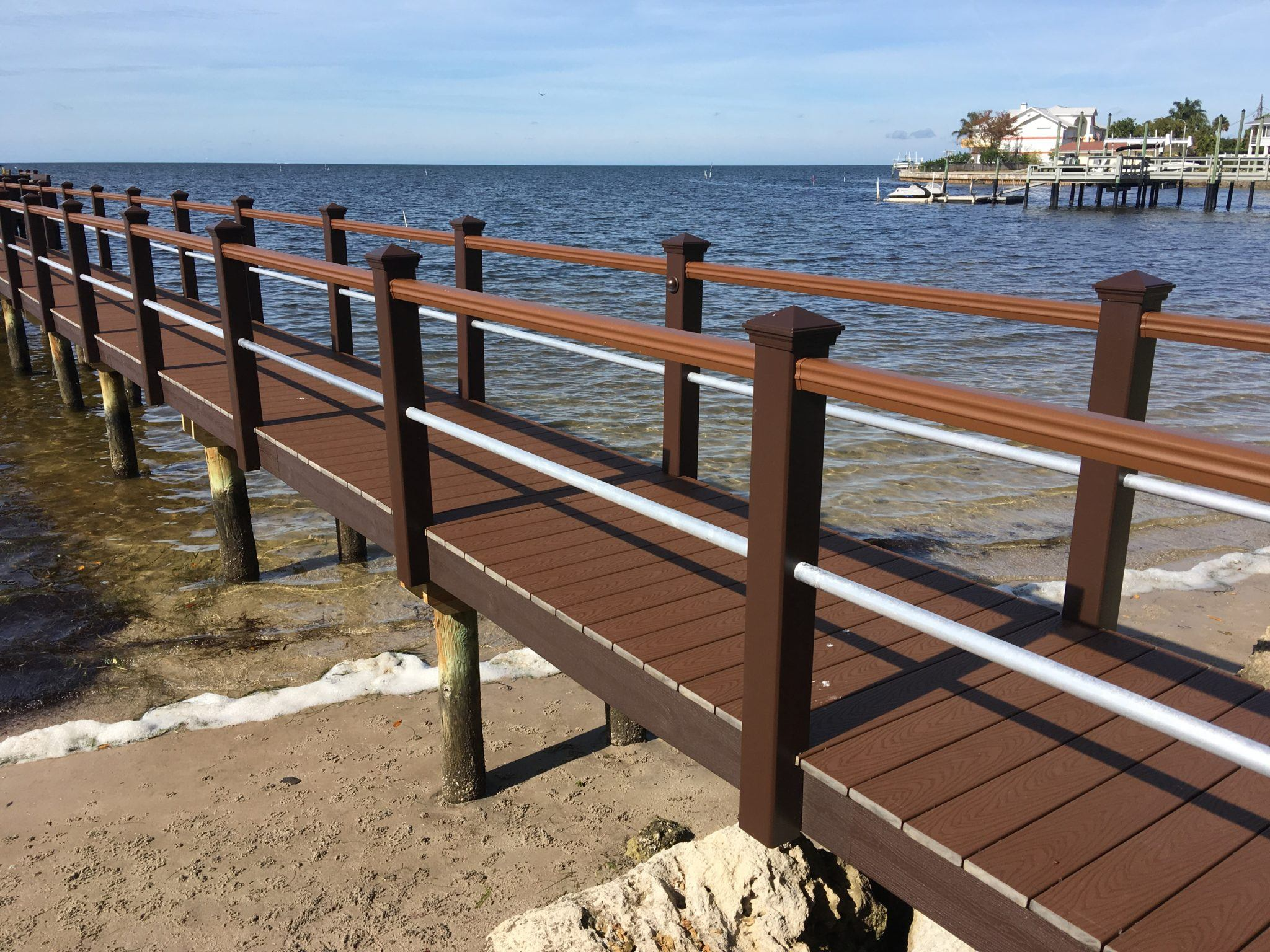 A stationary dock with Trex decking and Trex and aluminum pipe handrail down the sides over the water