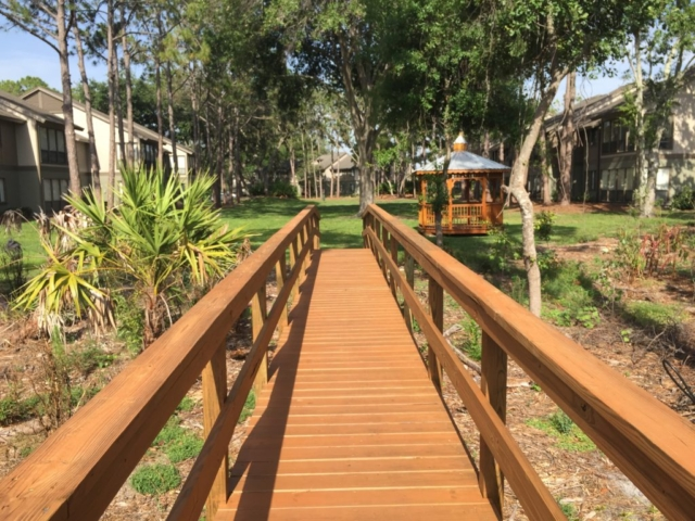 A wooden timber boardwalk that lands on a grass park with a gazebo next to it
