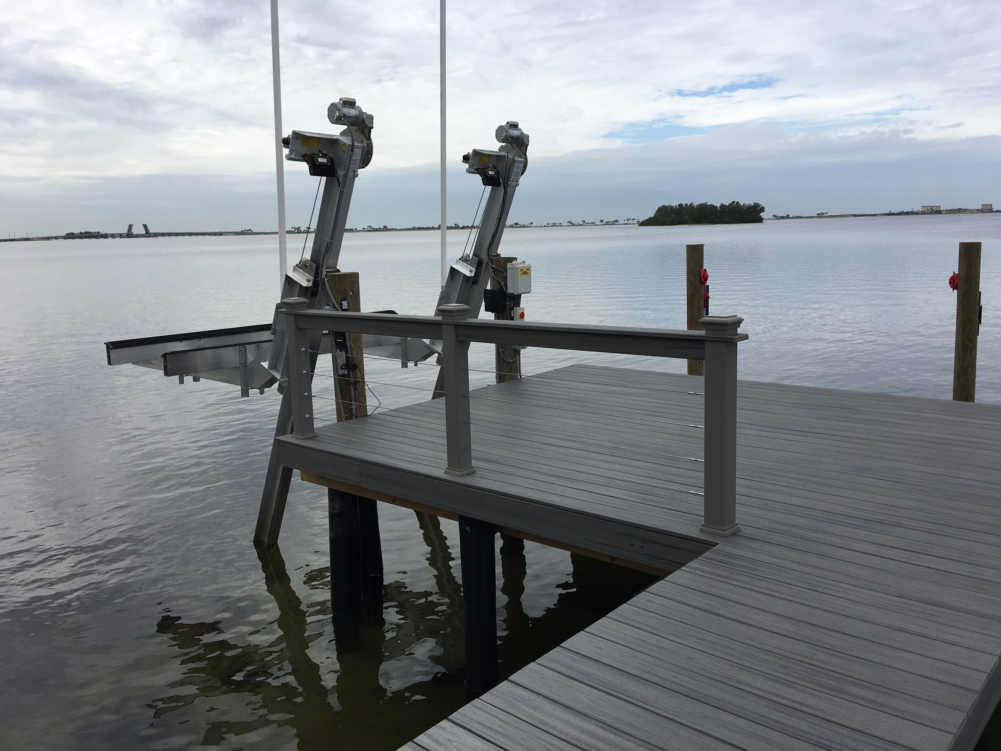 Elevator aluminum boat lift attached to stationary dock on the water