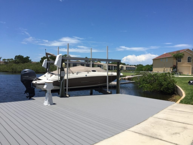 Stationary dock with composite Trex decking with a boat lift on the water
