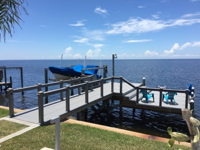 Stationary dock over the water with Trex composite decking and hand railing with cables