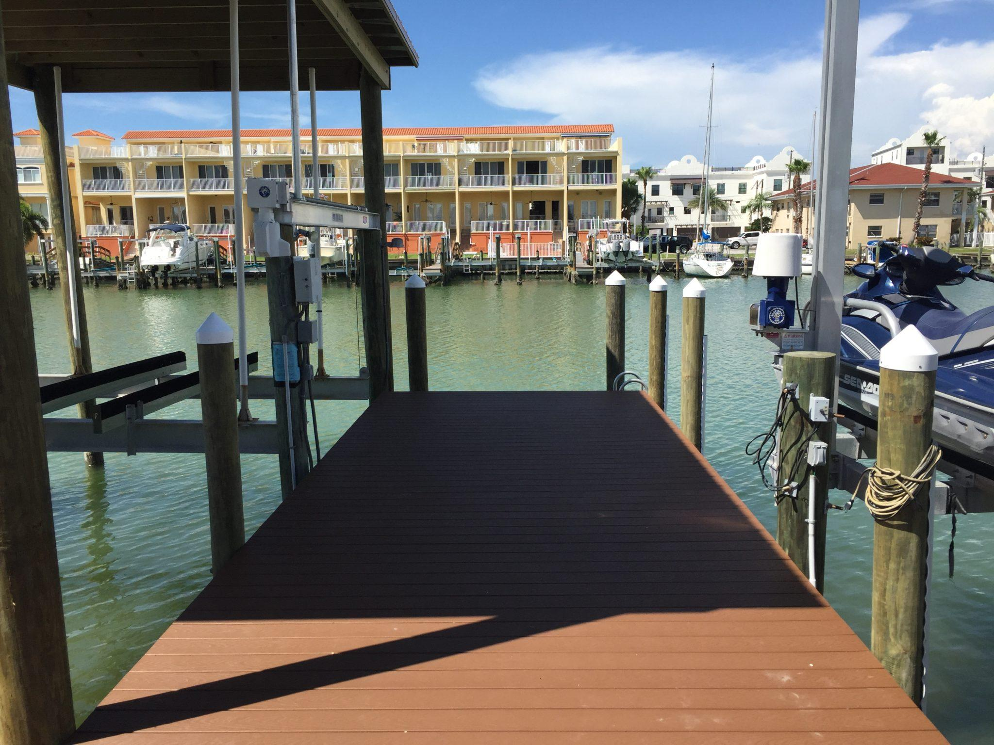 Stationary dock with composite Trex decking with a roof and jet ski lift on the water