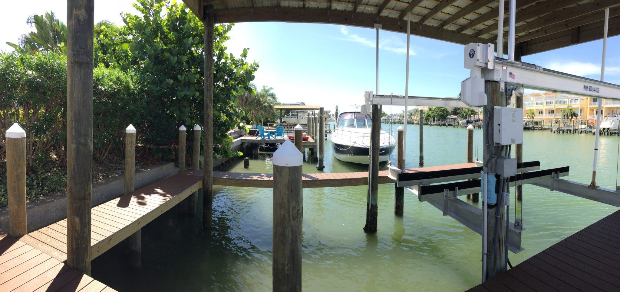 Stationary dock with composite Trex decking with catwalk around boat lift on the water