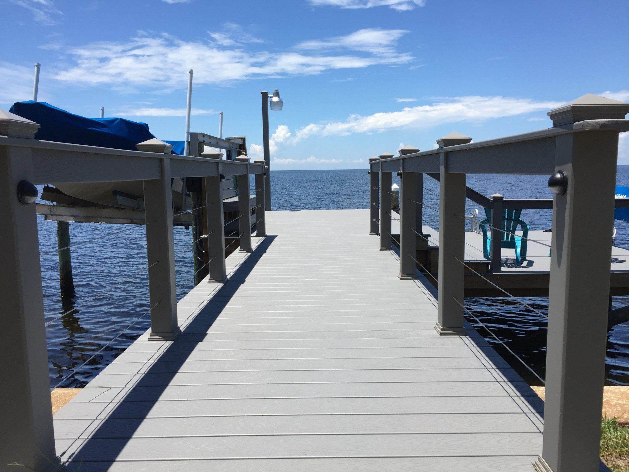 Composite Trex hand railing with stainless steel cables on a stationary dock on the water