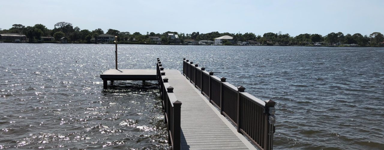 A stationary dock with Trex composite decking and hand railing on the water