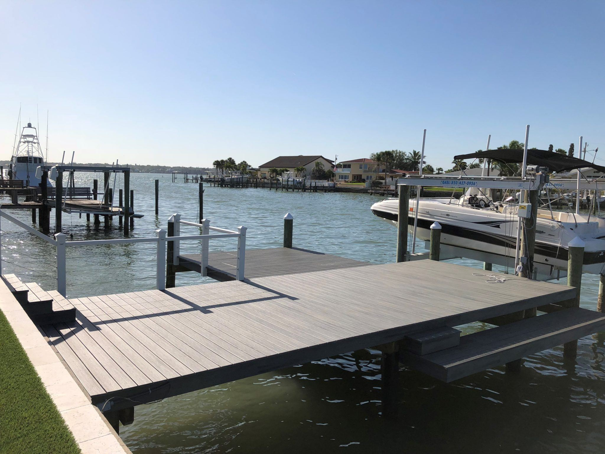 A stationary dock with Trex composite decking and stainless steel cable railing on the water
